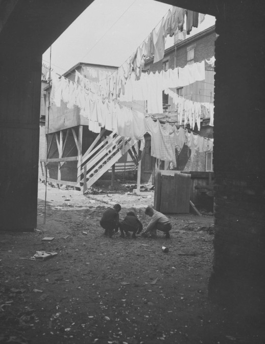 Black-and-white photograph showing a courtyard with laundry hanging from various clotheslines. Three children are playing on the ground.