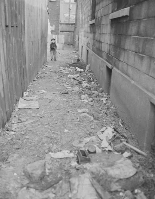 Black-and-white photograph showing a long, narrow lane strewn with garbage. A young child stands at the far end looking at the viewer.