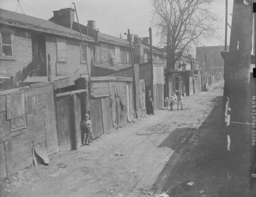 Black-and-white photograph showing the dilapidated back lane behind the row houses. Children look towards the viewer.