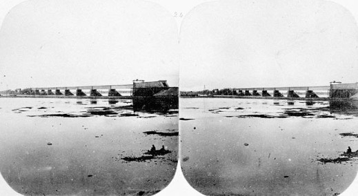 Black-and-white stereoscopic photograph showing the construction of a bridge.