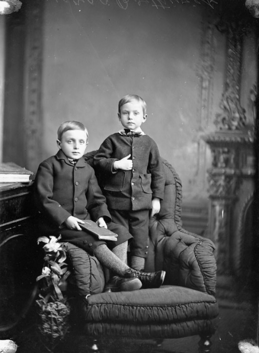 Black-and-white photograph of two young boys in black jackets, one seated and one standing on a chair.