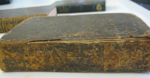 A colour photograph showing several books on a table. The book in the foreground has extremely deteriorated leather and the spine has separated from the front cover.