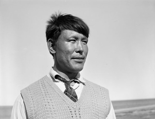 Black-and-white photograph of a close-up of an Inuit man wearing a knitted vest and tie standing outside.