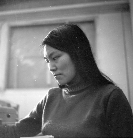 Photograph of a young Inuit woman wearing a turtle neck sweater looking away from the camera.