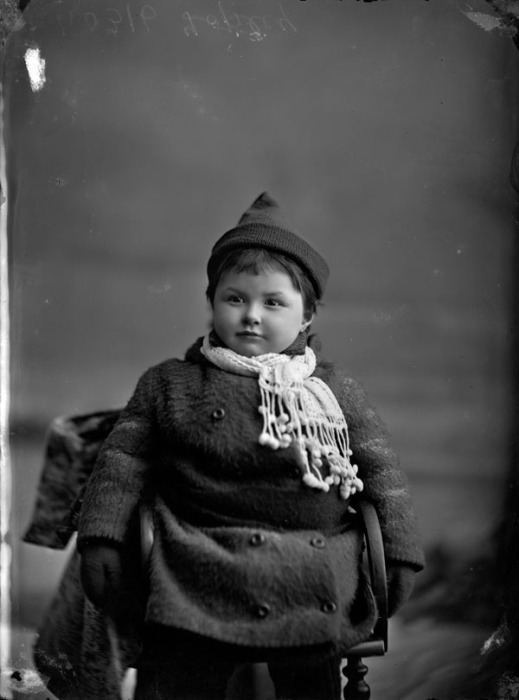 Black-and-white photograph of a young girl dressed in winter clothing.