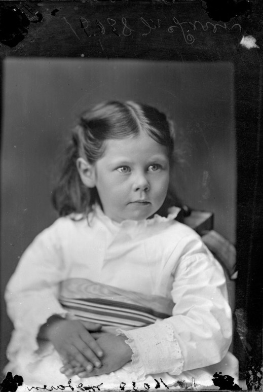 Black-and-white photograph of a young girl in a white dress.