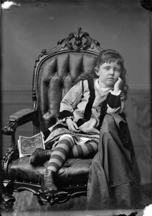 Black-and-white photograph of a young girl with her chin resting on her hands, a book beside her.