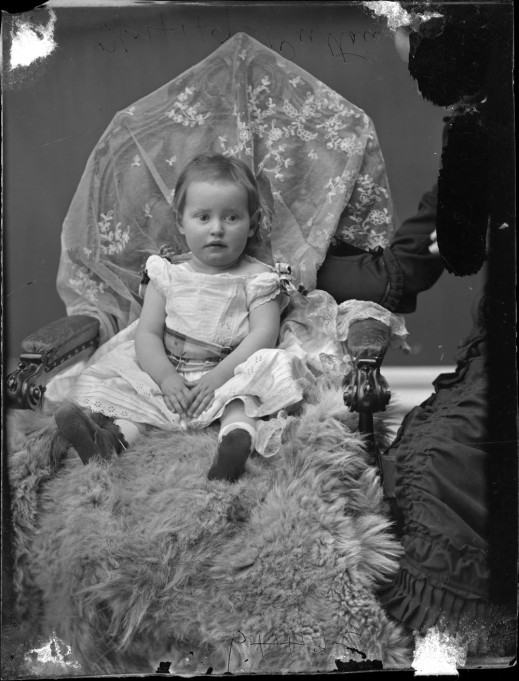 Black-and-white photograph of a young child with the mother to the right, partially blacked out.