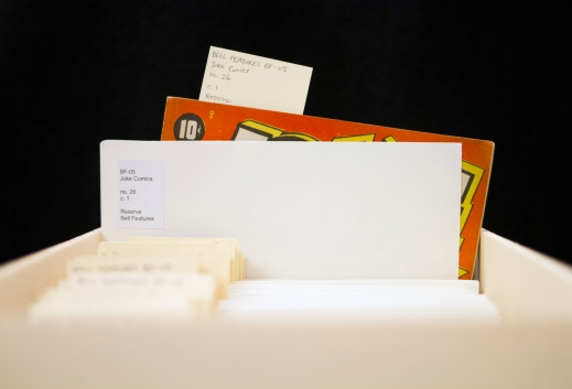 Colour photograph showing a filing box with folders with labels, one is pulled out half-way and a red comic book with the 10¢ price peeks out of the folder.