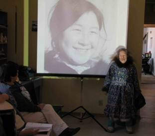 Colour photograph of an elderly Inuit woman wearing a fur-trimmed floral parka posing in front of a screen with a slide projection of her photograph when she was a young woman, taken at a community hall.