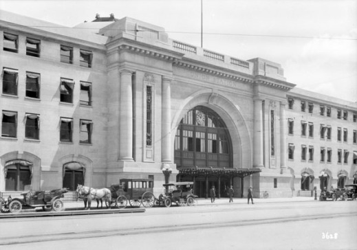 A black-and-white photograph showing the entrance to an imposing building. Automobiles and horse-drawn buggies are lined outside, and people are standing near the entrance.