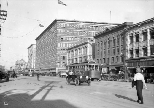A black-and-white photograph showing a wide street, busy with streetcars, automobiles, horse-drawn buggies, cyclists and pedestrians. The buildings along the street look new and prosperous.