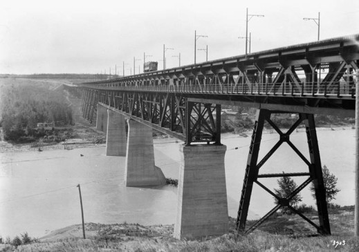 A black-and-white photograph showing a high-level railway bridge spanning a river.