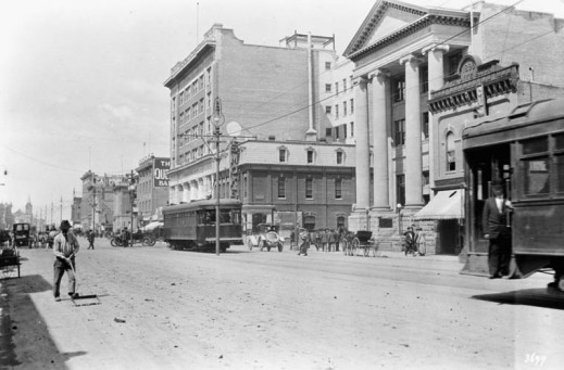 A black-and-white photograph showing a wide avenue, roughly paved, where streetcars, horse-drawn carriages and automobiles share the road. It is a streetscape bustling with activity.