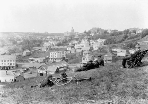 A black-and-white photograph taken from a hillside overlooking a town, showing cyclists resting on the grass and other men seated nearby.