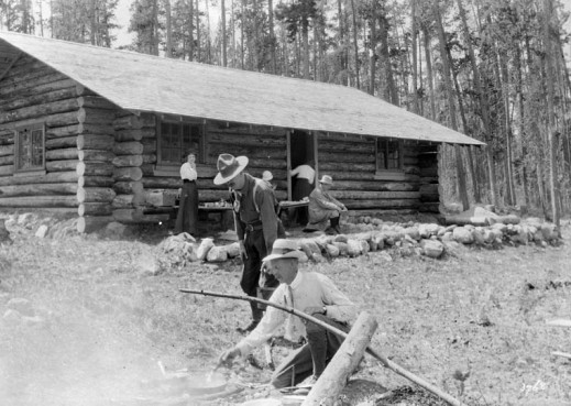 A black-and-white photograph of a group of people outside a rustic log cabin.
