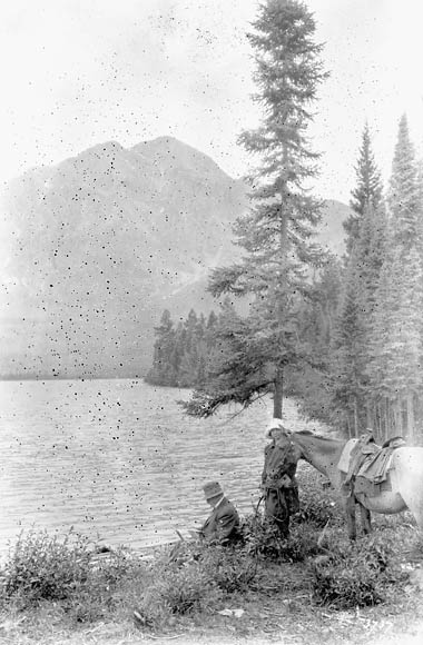 A black-and-white photograph showing a man and a woman with a horse by a lake. The man is seated and the woman is holding the lead to the horse. There are tall coniferous trees behind them.