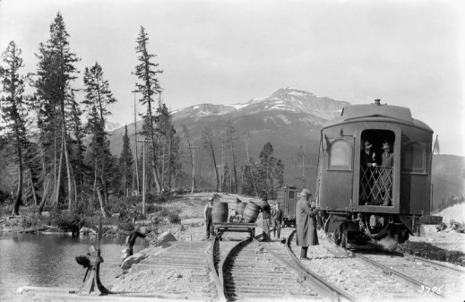 A black-and-white photograph showing a train stopped beside a river.