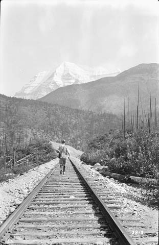 A black-and-white photograph showing a man walking along train tracks, with a view of Mount Robson in the distance.A black-and-white photograph showing a man walking along train tracks, with a view of Mount Robson in the distance.