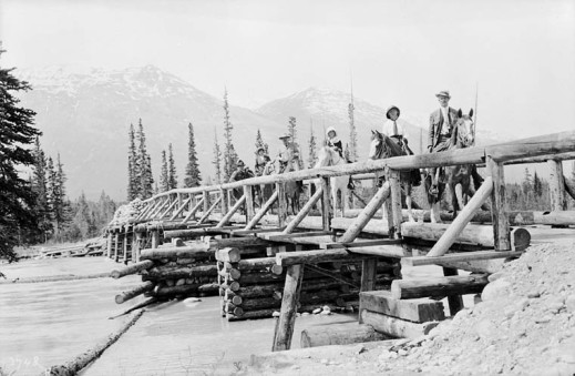 A black-and-white photograph showing one person walking and five people on horseback, on a log bridge crossing a river, with mountains in the background.