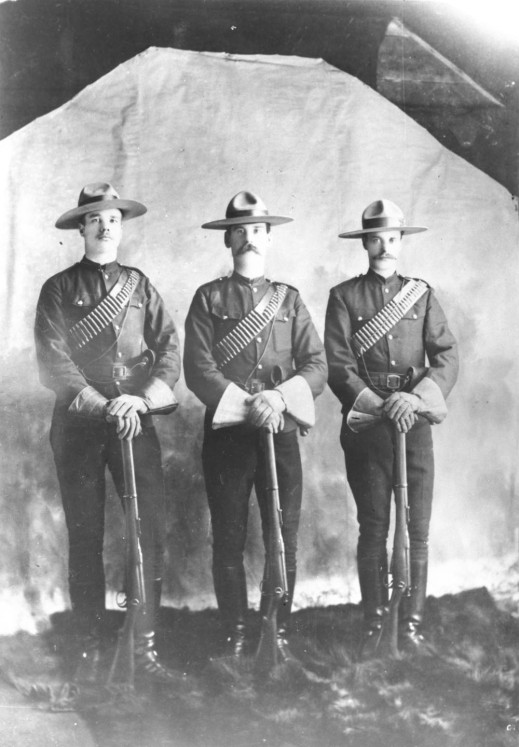Three North West Mounted Police constables in uniform standing at ease with clasped hands over the muzzles of their rifles.