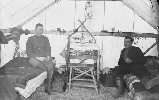 Black-and-white photograph of two men in North West Mounted Police uniform sitting on cots in a tent