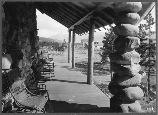 A black-and-white photograph showing a veranda with seating to take advantage of the view. The architectural style is rustic, with river stones and rough-hewn beams.