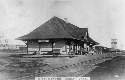 A black-and-white photograph of a train station taken from the other side of the tracks. There is a sign with the word Biggar, and there's a note at the bottom of the photograph identifying it as G.T.P. Station, Biggar, Sask.