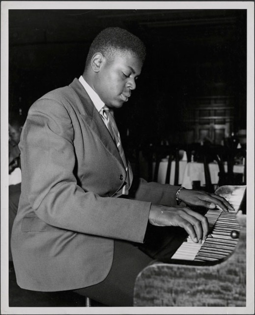 A black-and-white photograph showing Oscar Peterson playing the piano in a lounge.