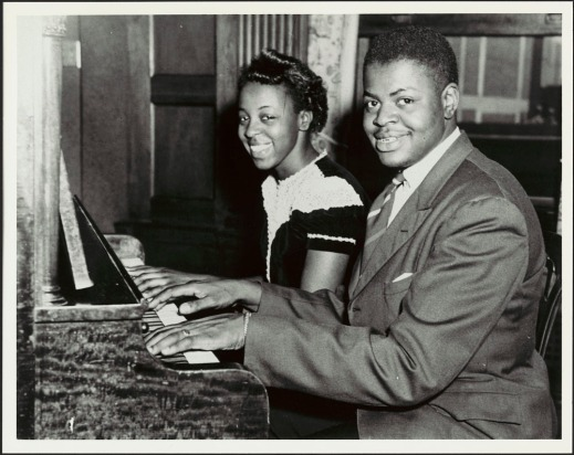 A black-and-white photograph of Oscar Peterson and his sister Daisy seated at the piano with their hands on the keyboard. They are looking at the camera and smiling.