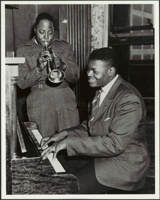 A black-and-white photograph showing Oscar Peterson seated, playing piano. His brother Charles, dressed in the uniform of the Canadian Army, stands next to him playing the trumpet.