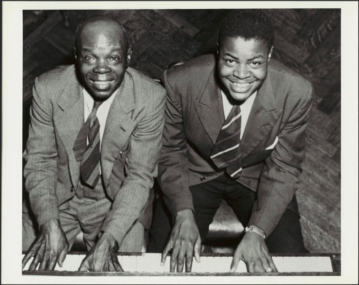 A black-and-white photograph showing Oscar Peterson with his father, Daniel. Both men are sitting at a piano, with their hands on the keyboard, smiling and looking up at the camera.