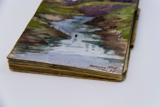 "A colour photograph of a sketchbook at an angle showing a riverbank with the date and location in the lower right corner, ""Perrone April 17."""