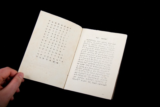 A colour image of a book written in Inuktitut syllabic script open to the first and second pages. The left page features the Inuktitut syllabary; the right page is text written in Inuktitut syllabic.