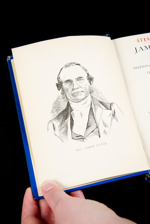 A colour photograph showing a hand holding the lower left corner of a book. The book is opened to the frontispiece showing a drawn portrait of Methodist missionary James Evans, wearing typical 19th century clothing and looking directly at the viewer.