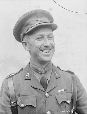 A black-and-white photograph showing a man smiling broadly in an officer's uniform with cap.