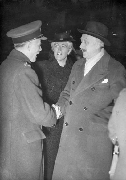 A black-and-white photograph of two men and a woman. The men are shaking hands and the woman is looking at one of the men.