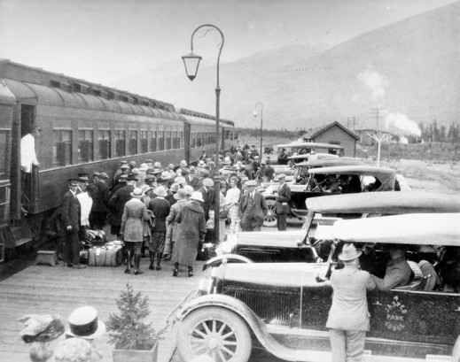 "A black-and-white photograph of a crowd of people with baggage standing on the platform next to a passenger train. Two porters are seen beside the train. One is on the platform attending to some luggage; the other stands in the doorway of the train. An automobile in the foreground has a sign on the door reading ""Jasper Park Lodge."" Mountains are visible in the distance."