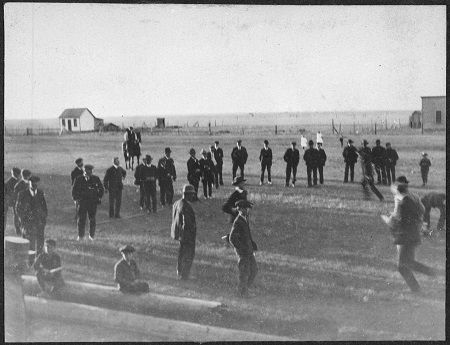 A black-and-white photograph of a group of men standing in a field watching a game of duck on the rock.