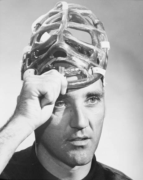 A black-and-white photograph of a man taking off a goalie mask.