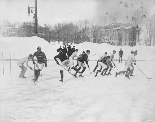 A black-and-white photograph showing hockey players during a game on an outdoor hockey rink
