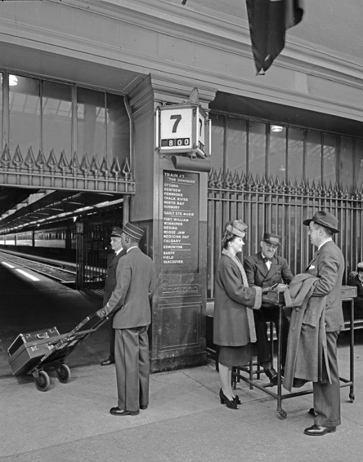"A black-and-white photograph of people in a train station. A porter, with luggage on a dolly, is facing away from the camera. Two well-dressed travellers are speaking to a ticket agent. An information board with destinations is on the wall behind the travellers announcing the train as ""The Dominion"" from Montréal to Vancouver. A passenger train is visible in the background."