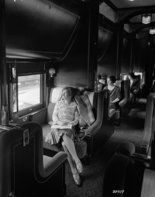 A black-and-white photograph of people seated in a railway sleeping car, looking out the windows.