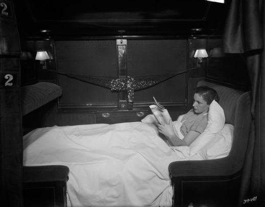 A black-and-white photograph of a woman, in profile, lying under the blankets in the lower bunk reading a newspaper.