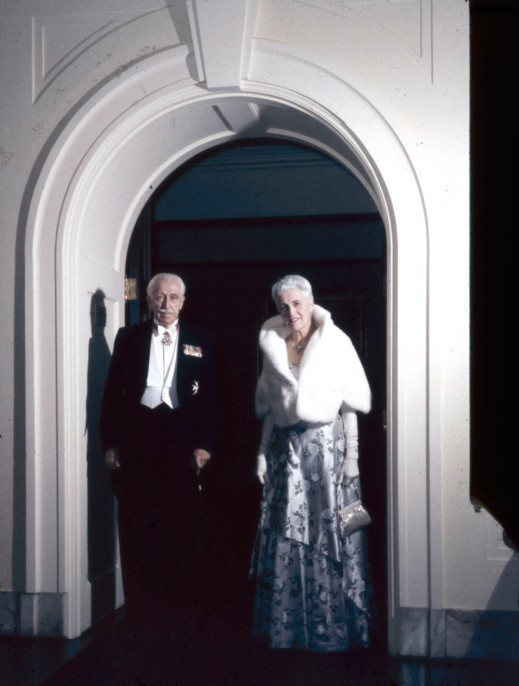 A colour photograph showing a couple standing in a doorway in evening dress looking directly at the photographer.