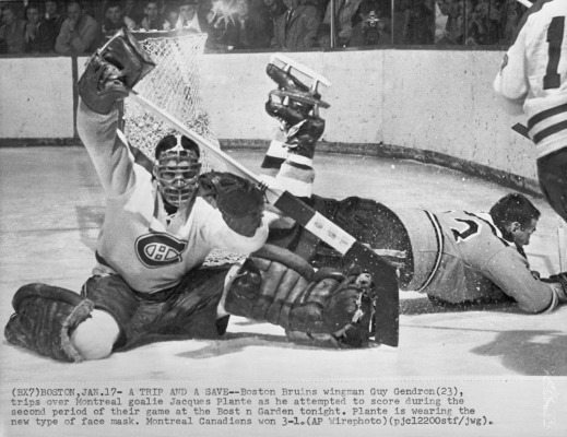 A black-and-white photograph of a goalie with a mask defending his net. Behind him other players (without helmets) are falling on the ice, reaching for the puck.