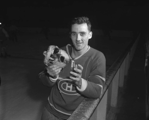 A black-and-white photograph of a man leaning on the hockey boards holding a transparent mask in his hands.