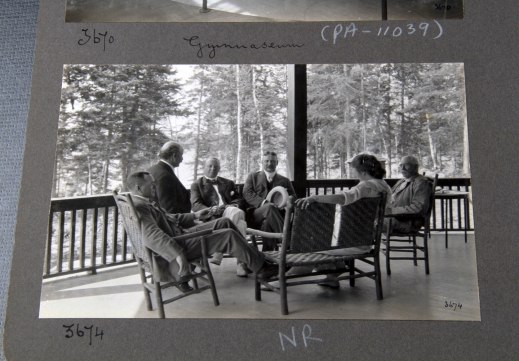 A black-and-white photograph showing a group of people sitting on a veranda overlooking a wooded area.