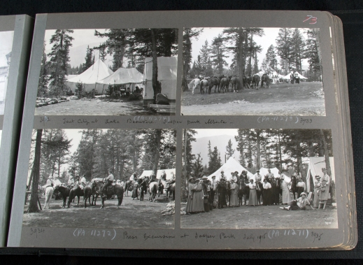 A photograph of a photo album, showing four black-and-white photographs of groups of people with horses and tents.