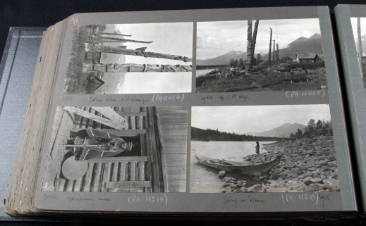 A photograph of an album, showing four black-and-white photographs of various scenes in British Columbia, including the totem poles at Kitwanga, a view of the village, an unidentified medicine man and a person fishing on a stream.